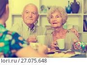 Купить «Happy mature couple drinking tea with female guest», фото № 27075648, снято 28 августа 2017 г. (c) Яков Филимонов / Фотобанк Лори