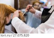 Купить «Hairdresser leveling and cutting hair to young blonde woman with use of scissors», фото № 27075820, снято 7 марта 2017 г. (c) Яков Филимонов / Фотобанк Лори