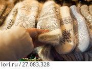 Купить «woman buying woolen mittens at christmas market», фото № 27083328, снято 1 декабря 2016 г. (c) Syda Productions / Фотобанк Лори