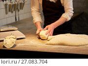 Купить «baker portioning dough with bench cutter at bakery», фото № 27083704, снято 15 мая 2017 г. (c) Syda Productions / Фотобанк Лори