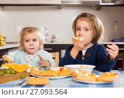 Купить «Two little girls enjoying pastry with cream», фото № 27093564, снято 14 декабря 2018 г. (c) Яков Филимонов / Фотобанк Лори