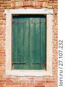 Закрытое окно со старыми зелеными деревянными ставнями в кирпичной стене солнечным днем (2017 год). Стоковое фото, фотограф Виктор Карасев / Фотобанк Лори