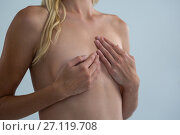 Купить «Mid section of shirtless young woman covering breast», фото № 27119708, снято 26 апреля 2017 г. (c) Wavebreak Media / Фотобанк Лори