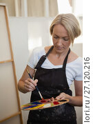 Купить «Woman holding palette and paintbrush in drawing class», фото № 27120216, снято 21 апреля 2017 г. (c) Wavebreak Media / Фотобанк Лори