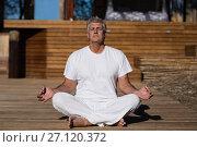 Купить «Man practicing yoga on wooden plank», фото № 27120372, снято 12 мая 2017 г. (c) Wavebreak Media / Фотобанк Лори