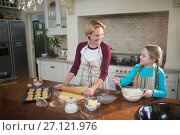 Smiling mother and daughter preparing cookies in kitchen. Стоковое фото, агентство Wavebreak Media / Фотобанк Лори
