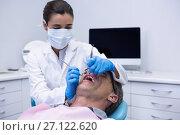 Купить «Doctor giving dental treatment to patient at clinic», фото № 27122620, снято 11 декабря 2016 г. (c) Wavebreak Media / Фотобанк Лори