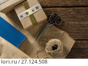 Купить «Paper with gift box by scissor and thread spool», фото № 27124508, снято 8 июня 2017 г. (c) Wavebreak Media / Фотобанк Лори
