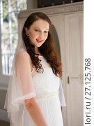 Купить «Portrait of happy bride in wedding dress at home», фото № 27125768, снято 2 мая 2017 г. (c) Wavebreak Media / Фотобанк Лори
