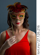 Купить «Woman wearing masquerade mask against black background», фото № 27126216, снято 22 мая 2017 г. (c) Wavebreak Media / Фотобанк Лори