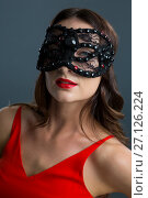 Купить «Woman wearing masquerade mask against black background», фото № 27126224, снято 22 мая 2017 г. (c) Wavebreak Media / Фотобанк Лори