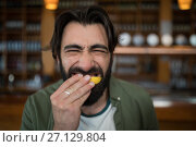 Купить «Man biting into lemon wedge after having tequila shot», фото № 27129804, снято 22 августа 2017 г. (c) Wavebreak Media / Фотобанк Лори