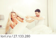 Купить «happy couple having pillow fight in bed at home», фото № 27133280, снято 25 февраля 2016 г. (c) Syda Productions / Фотобанк Лори