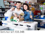 Купить «couple demonstrating tools for house renovating in paint store», фото № 27133348, снято 9 марта 2017 г. (c) Яков Филимонов / Фотобанк Лори