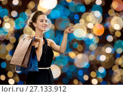 Купить «happy woman in black dress with shopping bags», фото № 27133912, снято 1 июня 2014 г. (c) Syda Productions / Фотобанк Лори