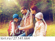Купить «happy family with backpacks and thermos at camp», фото № 27141664, снято 27 сентября 2015 г. (c) Syda Productions / Фотобанк Лори