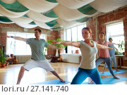 Купить «group of people doing yoga warrior pose at studio», фото № 27141740, снято 5 марта 2017 г. (c) Syda Productions / Фотобанк Лори
