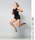 Купить «young woman in black sportswear jumping», фото № 27141780, снято 26 апреля 2017 г. (c) Syda Productions / Фотобанк Лори