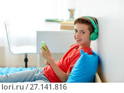 Купить «happy boy with smartphone and headphones at home», фото № 27141816, снято 10 июня 2017 г. (c) Syda Productions / Фотобанк Лори