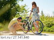 Купить «young couple fixing bicycle on country road», фото № 27141840, снято 23 июля 2017 г. (c) Syda Productions / Фотобанк Лори