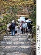 Купить «Посетители с зонтами прогуливаются на территории Золотого павильона (Kinkaku-ji) в дождливую погоду. Киото, Япония», фото № 27143368, снято 12 апреля 2013 г. (c) Кекяляйнен Андрей / Фотобанк Лори