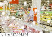 Купить «couple with shopping cart buying meat at grocery», фото № 27144844, снято 21 октября 2016 г. (c) Syda Productions / Фотобанк Лори