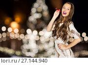 Купить «woman with party blower over christmas tree lights», фото № 27144940, снято 31 октября 2015 г. (c) Syda Productions / Фотобанк Лори