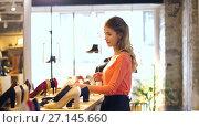 Купить «happy young woman choosing shoes at store», видеоролик № 27145660, снято 6 октября 2017 г. (c) Syda Productions / Фотобанк Лори