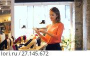Купить «happy young woman choosing shoes at store», видеоролик № 27145672, снято 6 октября 2017 г. (c) Syda Productions / Фотобанк Лори