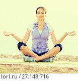 Купить «Smiling woman practise yoga cross-legged», фото № 27148716, снято 22 июля 2018 г. (c) Яков Филимонов / Фотобанк Лори