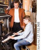 Купить «Father and teenage son examining keyboards in guitar shop», фото № 27152968, снято 29 марта 2017 г. (c) Яков Филимонов / Фотобанк Лори