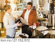 Купить «Father and teenage son examining drum units in guitar shop», фото № 27152972, снято 29 марта 2017 г. (c) Яков Филимонов / Фотобанк Лори