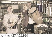 Купить «Father and teenage son examining drum units in guitar shop», фото № 27152980, снято 29 марта 2017 г. (c) Яков Филимонов / Фотобанк Лори