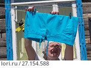 Женщина развешивает белье на веревку для сушки летом на солнце во дворе частного дома. Стоковое фото, фотограф Юлия Юриева / Фотобанк Лори