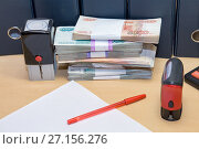Купить «Российские деньги, чистый лист бумаги, ручка, печати на столе. Налоговые и другие финансовые обязательства юридического лица», фото № 27156276, снято 3 августа 2017 г. (c) Наталья Осипова / Фотобанк Лори