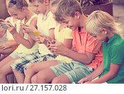 Купить «children in school age looking at mobile phones and sitting outd», фото № 27157028, снято 25 апреля 2018 г. (c) Яков Филимонов / Фотобанк Лори