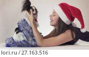 Купить «Beautiful teen girl in Santa Claus hat and dog Continental Toy Spaniel Papillon in New Year's tinsel joyfully playing on white background stock footage video», видеоролик № 27163516, снято 30 октября 2017 г. (c) Юлия Машкова / Фотобанк Лори