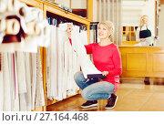 Купить «Adult woman choosing interesting fabric», фото № 27164468, снято 15 февраля 2017 г. (c) Яков Филимонов / Фотобанк Лори