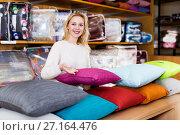 Купить «Woman seller displaying various home textiles», фото № 27164476, снято 15 февраля 2017 г. (c) Яков Филимонов / Фотобанк Лори