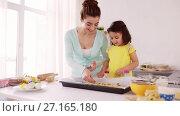 Купить «happy mother and daughter making cookies at home», видеоролик № 27165180, снято 20 августа 2019 г. (c) Syda Productions / Фотобанк Лори