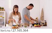 Купить «happy couple cooking and serving food at home», видеоролик № 27165364, снято 19 ноября 2017 г. (c) Syda Productions / Фотобанк Лори
