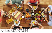 Купить «group of people eating at table with food», видеоролик № 27167896, снято 15 сентября 2019 г. (c) Syda Productions / Фотобанк Лори