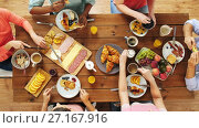 Купить «group of people eating at table with food», видеоролик № 27167916, снято 23 апреля 2019 г. (c) Syda Productions / Фотобанк Лори