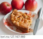 Кусок шарлотки лежит на тарелке на фоне яблок. Стоковое фото, фотограф Игорь Низов / Фотобанк Лори