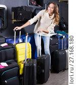 Купить «Young woman choosing travel suitcase in shop», фото № 27168180, снято 18 января 2019 г. (c) Яков Филимонов / Фотобанк Лори