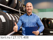 Купить «auto business owner and wheel tires at car service», фото № 27171408, снято 21 сентября 2017 г. (c) Syda Productions / Фотобанк Лори
