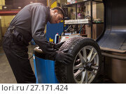 Купить «auto mechanic balancing car tire at workshop», фото № 27171424, снято 21 сентября 2017 г. (c) Syda Productions / Фотобанк Лори