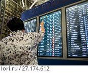 Женщина указывает рукой на табло с расписанием авиарейсов аэропорта Внуково (2017 год). Редакционное фото, фотограф Вячеслав Палес / Фотобанк Лори