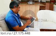 Купить «Senior man using digital tablet in living room 4k», видеоролик № 27175448, снято 17 января 2020 г. (c) Wavebreak Media / Фотобанк Лори