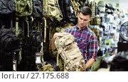 Купить «Man choosing textile backpack gun in military shop», видеоролик № 27175688, снято 14 июля 2017 г. (c) Яков Филимонов / Фотобанк Лори